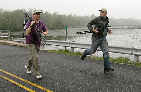 Team Sapsucker members Marshall Iliff, left, and team leader Chris Wood, both bird specialists from Cornell University's Lab of Ornithology, run with high-powered spotting scopes down a road that bisects a portion of Crystal Lake, N.J., during New Jersey Audubon's annual World Series of Birding, Saturday, May 9, 2009. The competitive fundraising event asks birders to identify as many species as they can by sight or sound in a 24-hour period. (AP Photo/Kathy Willens) WireSelects: 05/10/09